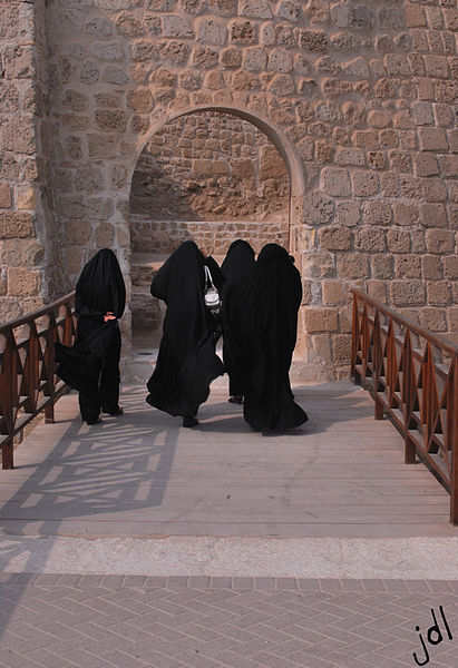 Four women clad in black, seen from the back, walking towards a stone gate in Bahrain / par Jayson De Leon. image sous licence creative commons, disponible sur Wikimedia commons ou Flickr.