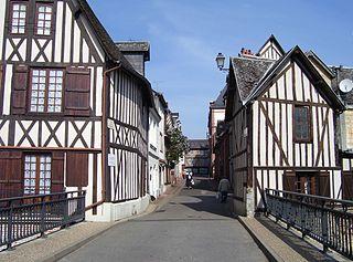 Maisons à la colombage à Bernay (Eure, France). Pont sur la Charentonne à l'ancienne porte de ville (porte de Boucheville/porte de Paris) par Stanzilla, photo sous licence Creative Commons disponible sur Wikimedia Commons